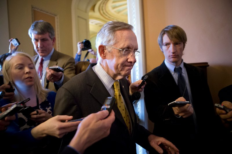 "Senate Majority Leader Harry Reid, D-Nev., retreats to a closed-door meeting with fellow Democrats as he and Senate Minority Leader Mitch McConnell, R-Ky., work to negotiate a legislative path to avoid the so-called ""fiscal cliff,"" at the Capitol in Washington on Sunday."