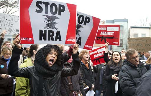 """Tasha Devoe, left, of Lawrence, Mass., joins a march to the National Rifle Association headquarters on Capitol Hill in Washington on Monday. After four days of self-imposed silence on the shooting that killed 26 people inside a Newtown, Conn., elementary school, the nation's largest gun rights lobby emerged Tuesday and promised """"to offer meaningful contributions to help make sure this never happens again."""""""