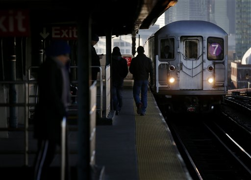 Commuters walk on the platform as a train enters the 40th Street-Lowry Street Station, where a man was killed after being pushed onto the subway tracks, in the Queens section of New York on Friday.