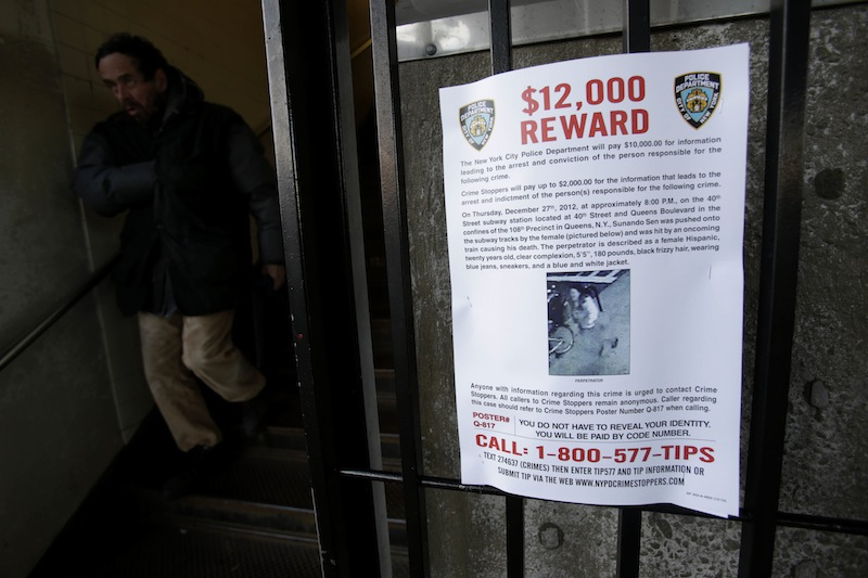 A reward poster is displayed on the entrance to the 40th St-Lowry St Station, where a man was killed after being pushed onto the subway tracks, in the Queens section of New York, Friday, Dec. 28, 2012. Police are searching for a woman suspected of pushing the man and released surveillance video Friday of her running away from the station. (AP Photo/Seth Wenig)