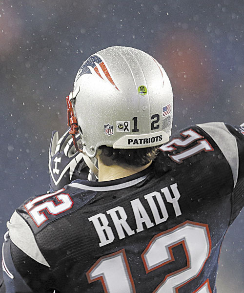 REMEMBERING: A sticker showing a black ribbon to honor the victims of the Sandy Hook Elementary School shootings in Newtown, Conn., is affixed to the helmet of New England Patriots quarterback Tom Brady before a game against the San Francisco 49ers on Sunday night in Foxborough, Mass.