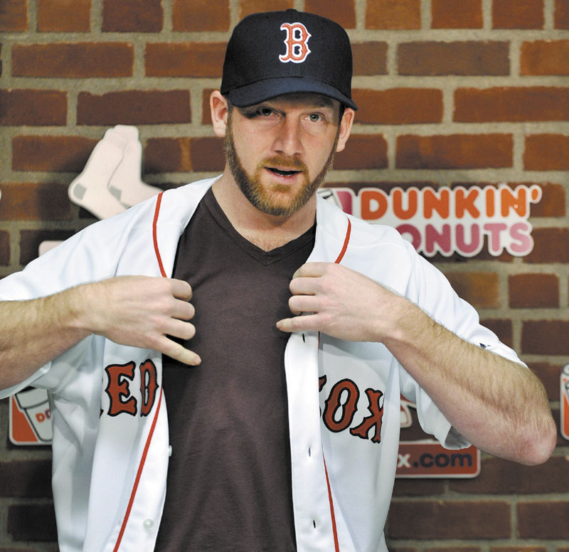 A NICE FIT: New Boston Red Sox pitcher Ryan Dempster puts on his jersey during a press conference Wednesday in Boston. Dempster signed a two-year, $26.5 million contract with the Red Sox.