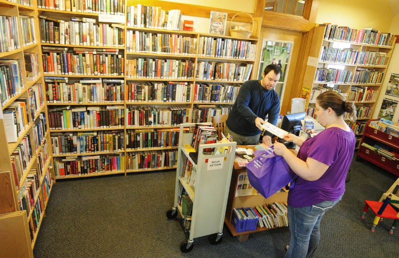 Belgrade library assistant Jared Bond, left, checks out books for Gina Davis on Thursday at the Belgrade Library, located in the Belgrade Community Center for All Seasons. The boxes at right are packed up for the upcoming move to the library's new Depot Road location, which will open Dec. 18.