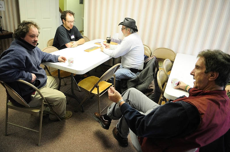 Steven Farrell, far left, chats with weekend manager Will Tibby, far right, as Jarody (who uses only on name), left, and Jim Duling play cribbage on opening day of the Augusta Community Warming Center on Sunday December 16, 2012 in downtown Augusta. The center, located at 44 Front St., across from the gazebo in Augusta's Waterfront Park, is open daily from 9 a.m. to 4 p.m.