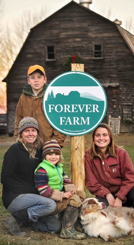 Mary Perry, left, and her children Gil Whitehead, standing, Sage Whitehead, seated on lap, and Kenya Whitehead, pose beside the Forever Farm sign at their Winterberry Farm, on Thursday in Belgrade.
