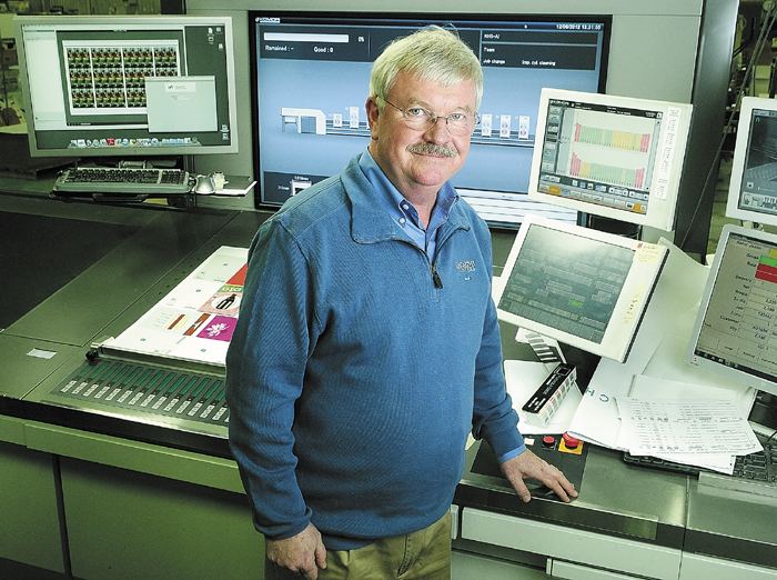 Rick Tardiff, president of J.S. McCarthy Printers, stands beside the control station of one of the company's Komori printing presses on Dec. 4 in Augusta.