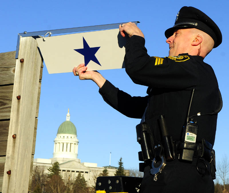 Augusta police Sgt. Christian Behr hangs a blue star, in honor of patrolman Eric Dos Santos, who is serving in Afghanistan on his second deployment with the Maine Army National Guard, on Saturday, at Augusta Police headquarters.