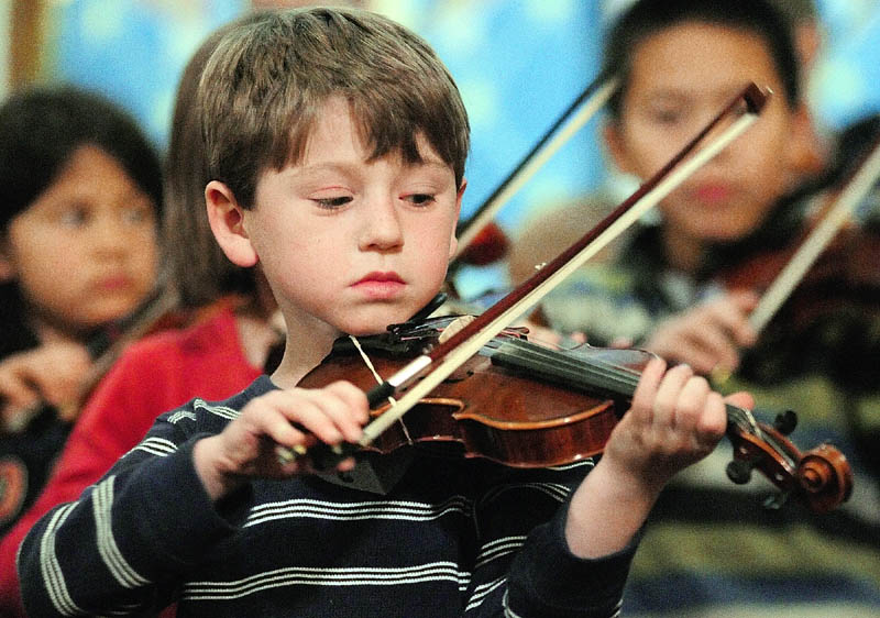 Ben Sheaffer plays his violin during a rehearsal of Pineland Suzuki School on Friday night at South Parish Congregational Church in Augusta.