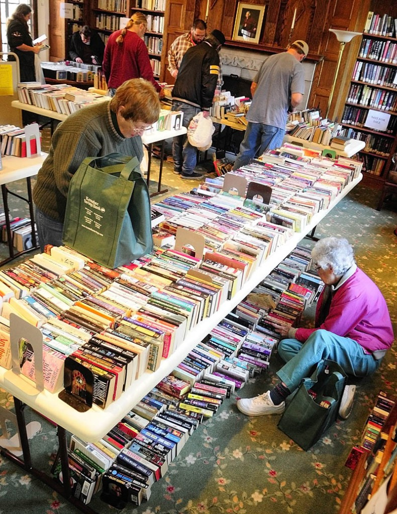 "Nan Spaulding, standing left, and Mary Perkins, seated right, look for books to buy on Monday morning at the Gardiner Public Library. Monday was a ""buck-a-bag"" sale day following the semiannual book sale held on Saturday. The next one will be held in June 2013, according to Library Director Anne Davis."