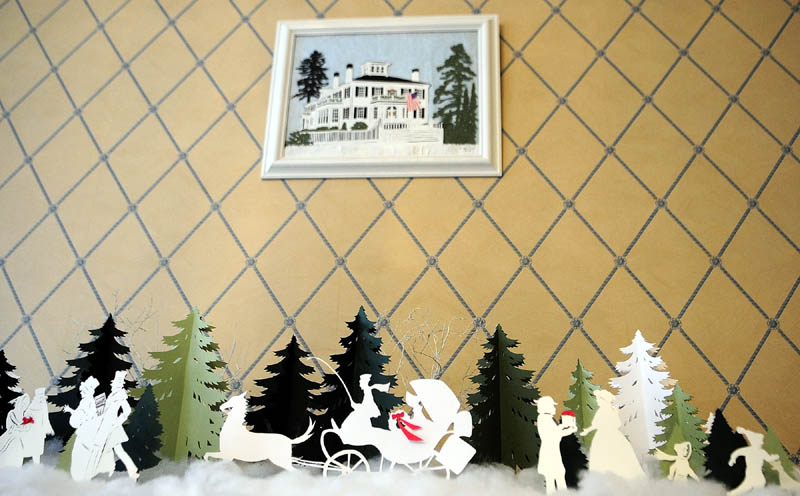 Cynthia Herrick made the picture of the Blaine House and the decoration on the table from cut paper, on display in the family dining room at the Blaine House on Tuesday in Augusta.