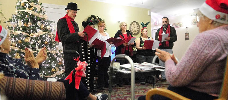 Connie Wing, left, and Eunice Dee clap for the Cosmic Carolers after they finished a song at the Hillside Terrace on Wednesday, in Hallowell. The group performs in the city's annual Christmas parade and this is the eigth year that the Cosmic Carolers have performed at several assisted-living and nursing homes in Hallowell.