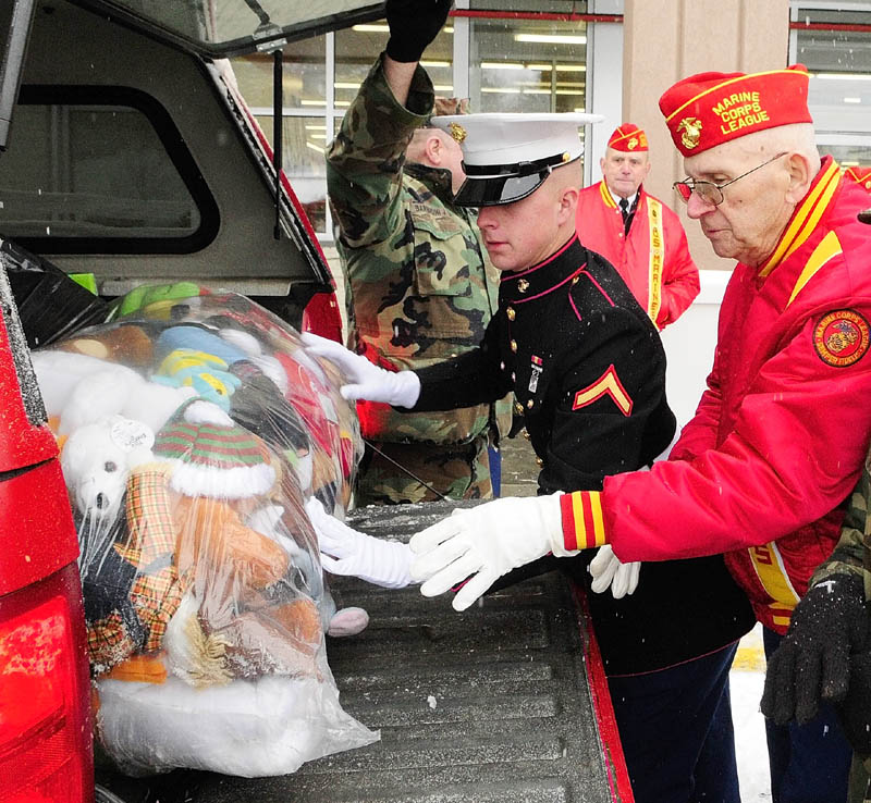 Marine Pfc. Evan Goodwin, left, and Marine Corps League member Dana Walls, of West Gardiner, load a bag of toys donated for the Toys for Tots campaign into a vehicle in Augusta on Monday. Goodwin and another Marine were picking up the toys donated by the Western Maine Young Marines and the Marine Corps League Detachment 599.
