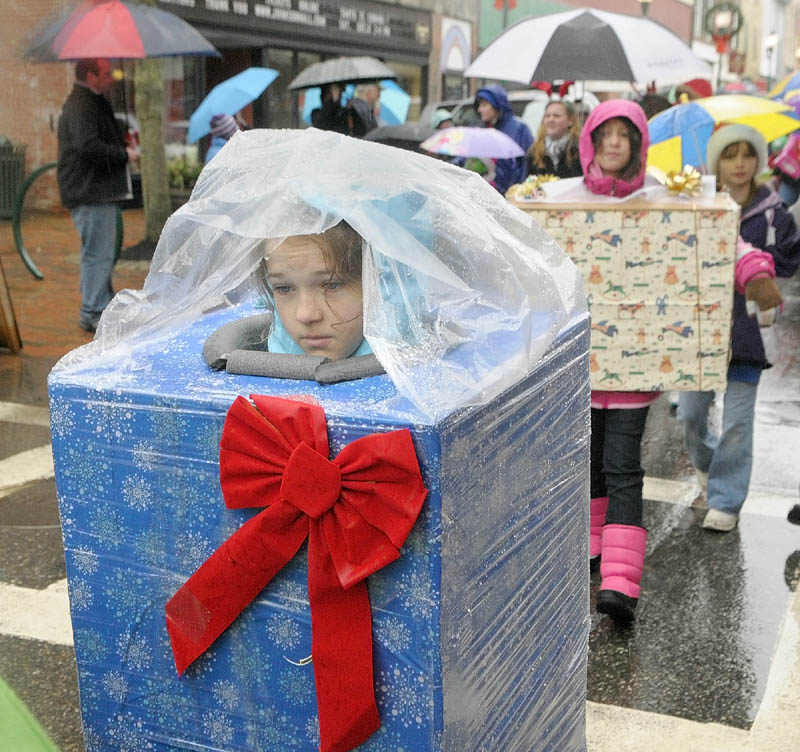 Thekla Jubinville wears a rain poncho over her wrapped present costume, as she marches down Water Street in the