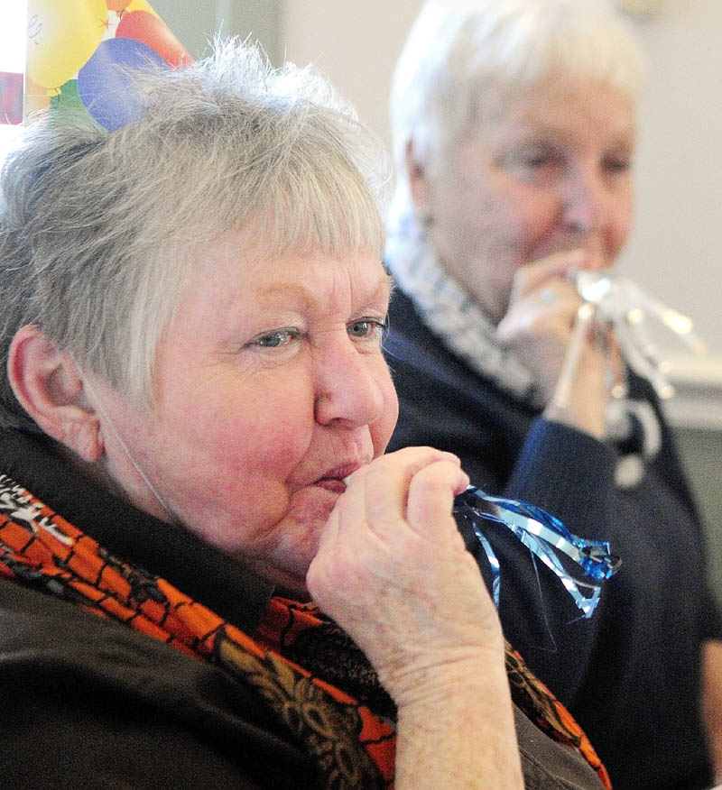 Joani Gavett, left, and Nancy Bunker, both of Mount Vernon, ring in the New Year by blowing noisemakers at noon on Monday at the Cohen Center in Hallowell. Organizers said noon here corresponded with midnight in Indonesia. About a 100 people attended the New Year's luncheon.