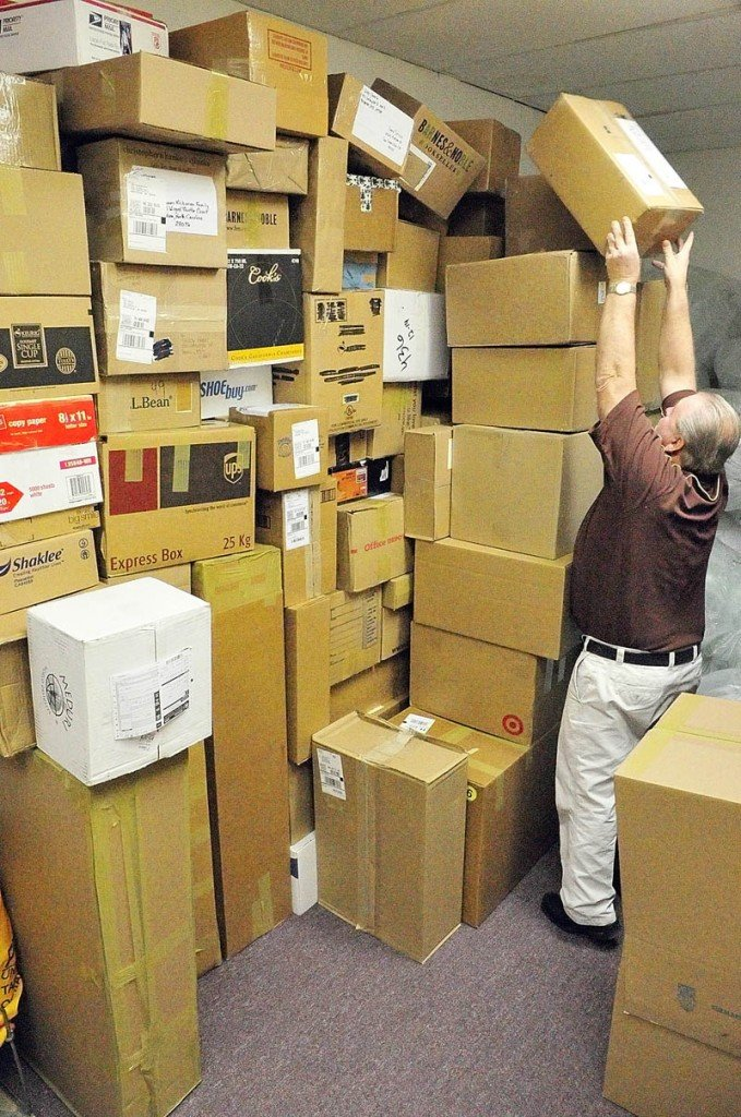 Keith McCray stacks another package on the pile waiting to be picked up by UPS The Mailing Center, his store in Shaw's Plaza in Augusta, on Monday. McCray joked that trying to stacked the different-shaped boxes was like a giant puzzle. He said that Monday is usually one of the busiest shipping days of the year, but the snowstorm had cut down on the number of customers coming in.