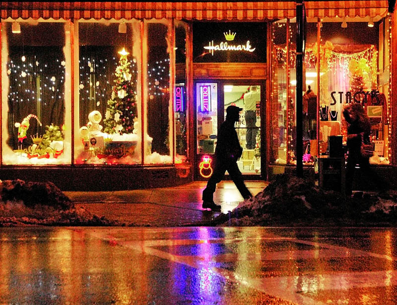People walk past the brightly decorated windows of Stacy's Hallmark on Water Street in downtown Augusta on Tuesday.