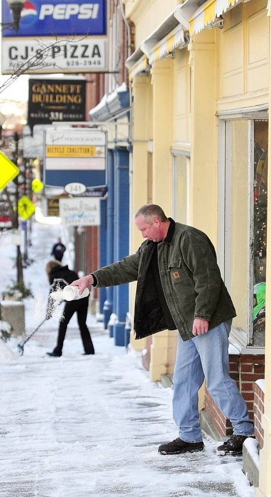 Augusta Pawn and Jewelry employee Troy Hanscom spreads salt in front of the store on Friday on Water Street in downtown Augusta. Building owner Karen Hatch shovels snow further up the street.