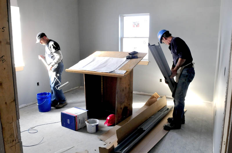 Art O'Brien, left, and Richard Hjort work on the Winslow police chief's office on Thursday.