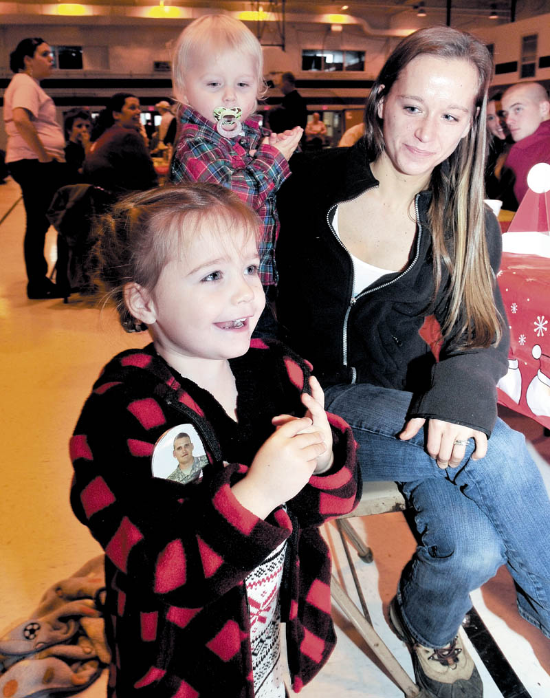 Cheyenne Allen, of Strong, wearing a button with a photo of her father, Sheldon Allen, reacts with joy as Santa enters the armory in Waterville on Sunday. Her mother, Emma, and brother, Elias, sit behind her during a family Christmas party for families of soldiers in the 488th Military Police Company, serving in Afghanistan.