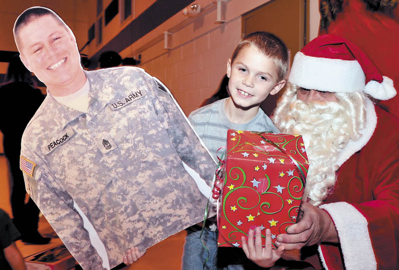 Colby Peacock had his hands full with a present from Santa and a large photo he brought of his father, 1st Sgt. Michael Peacock, during a Christmas party for families of soldiers in 488th Military Police Company, serving in Afghanistan, at the armory in Waterville on Sunday.