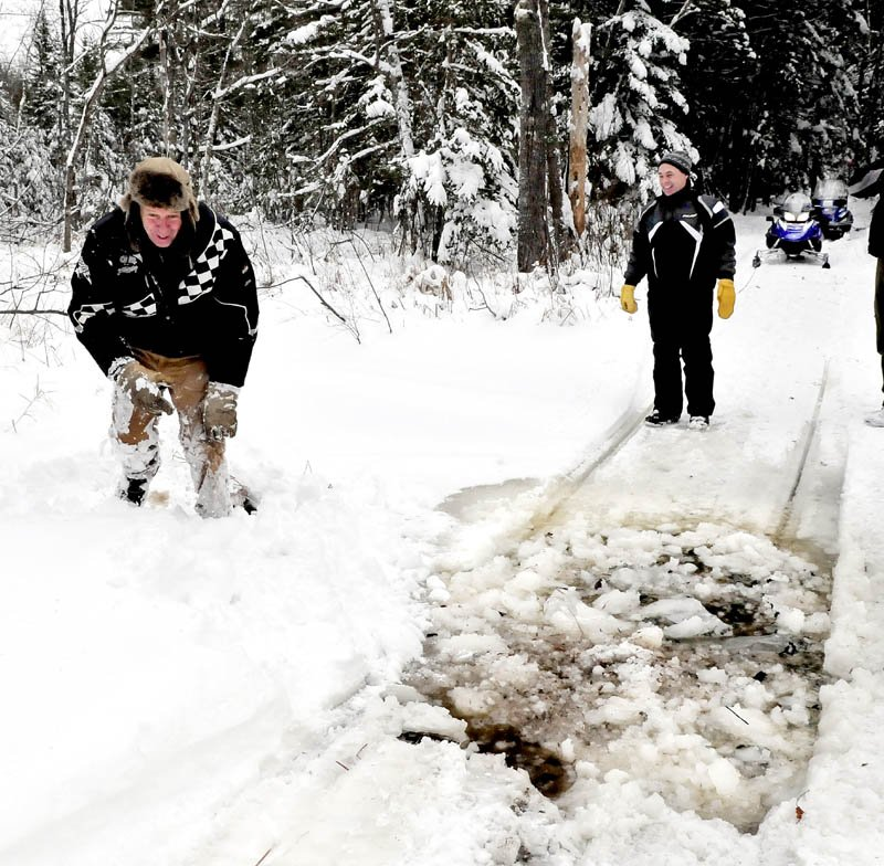 Belgrade Draggin Masters club member Ernie Rice, left, gets up after breaking through ice in a shallow stream along a snowmobile trail in Belgrade on Sunday. Dennis Harris waits to cross with his groomer.
