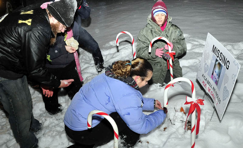 Staff photo by David Leaming REMEMBERED: Vigil organizer Karen Francis and others place candles at the base of a poster with a photo of missing toddler Ayla Reynolds outside the girls home in Waterville on Monday, Dec. 17, 2012. Reynolds was reported missing one-year ago.