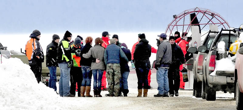 People seen hugging and holding each other approach Maine Warden Service personnel wearing survival suits, at the boat launch on Rangeley Lake on Monday. The body of Dawn Newell was recovered earlier in the day after her snowmobile went through the ice Sunday night.
