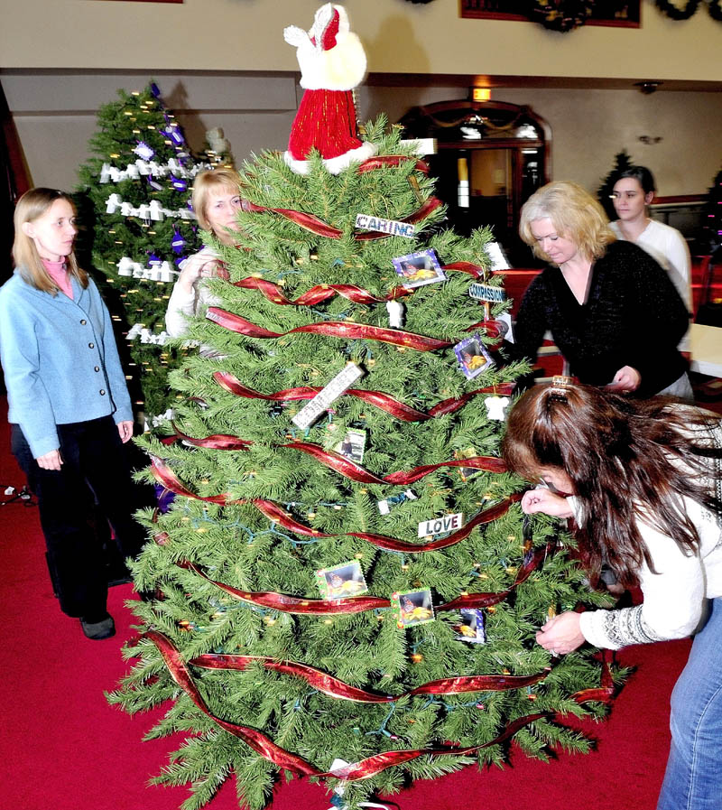 The Hospice Volunteers of Waterville Area decorate their tree at the Maine Academy of Natural Sciences at Good-Will Hinckley on Monday. From left are Sarah Swift, Barbara Radziewicz, Director Sue Roy, Jillian Roy, in back, and Deb Letourneau, at right.