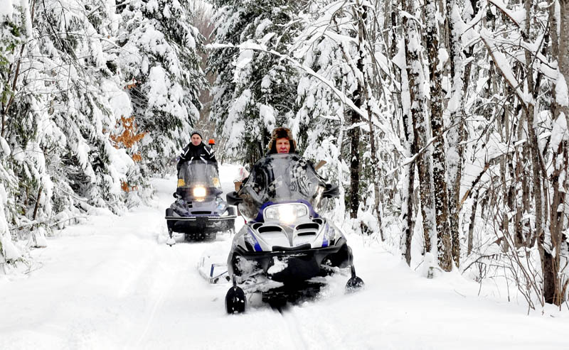 Ernie Rice, front, and Dennis Harris, both members of the Belgrade Draggin Masters club, groom snowmobile trails through the Belgrade woods on Sunday. The early and abundant snow is a blessing for area snowmobilers.