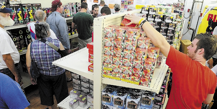 """Tyler Basinger. right, restocks shelves as customers line up to check out on at the Pyro City fireworks store in Manchester earlier this year. Scott Boucher, retail manager at the store, said that there were people waiting out in the parking lot before they opened Tuesday. """"We're staying busy and everybody's happy,"""" he said. The store is open daily from 9 a.m. to 9 p.m. through Sunday July 8th. This is the first Independence Day since the state legislature passed a law legalizing consumer fireworks last year."""