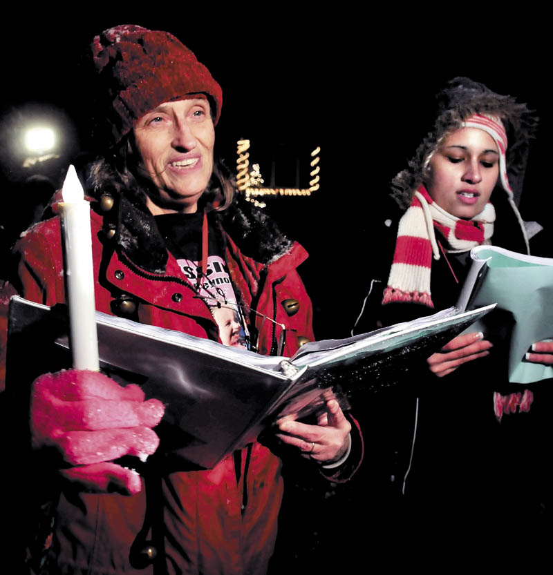 Glenda Armandi, left, and Jessica Verdejo join two dozen other people in singing Christmas carols on Monday outside the home at 29 Violette Ave. in Waterville, where toddler Ayla Reynolds was reported missing one year ago.