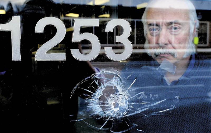 Jeff Rose, business manager for the International Brotherhood of Electrical Workers Local 1253, on Monday is seen behind one of seven bullet holes that shattered windows and walls at the office on Main Street in Fairfield. Someone shot at the building last Thursday evening while the office was occupied. There were no injuries.