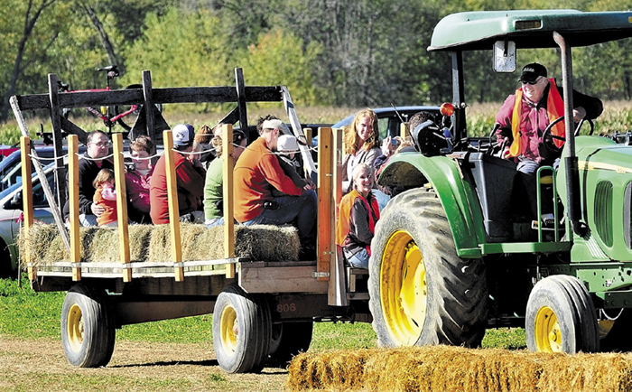 """Herbert """"Bussie"""" York waits on his tractor as families fill a haywagon for the trip to the pumpkin patch at his Amazing Maize corn maize off Route 2 in Farmington."""