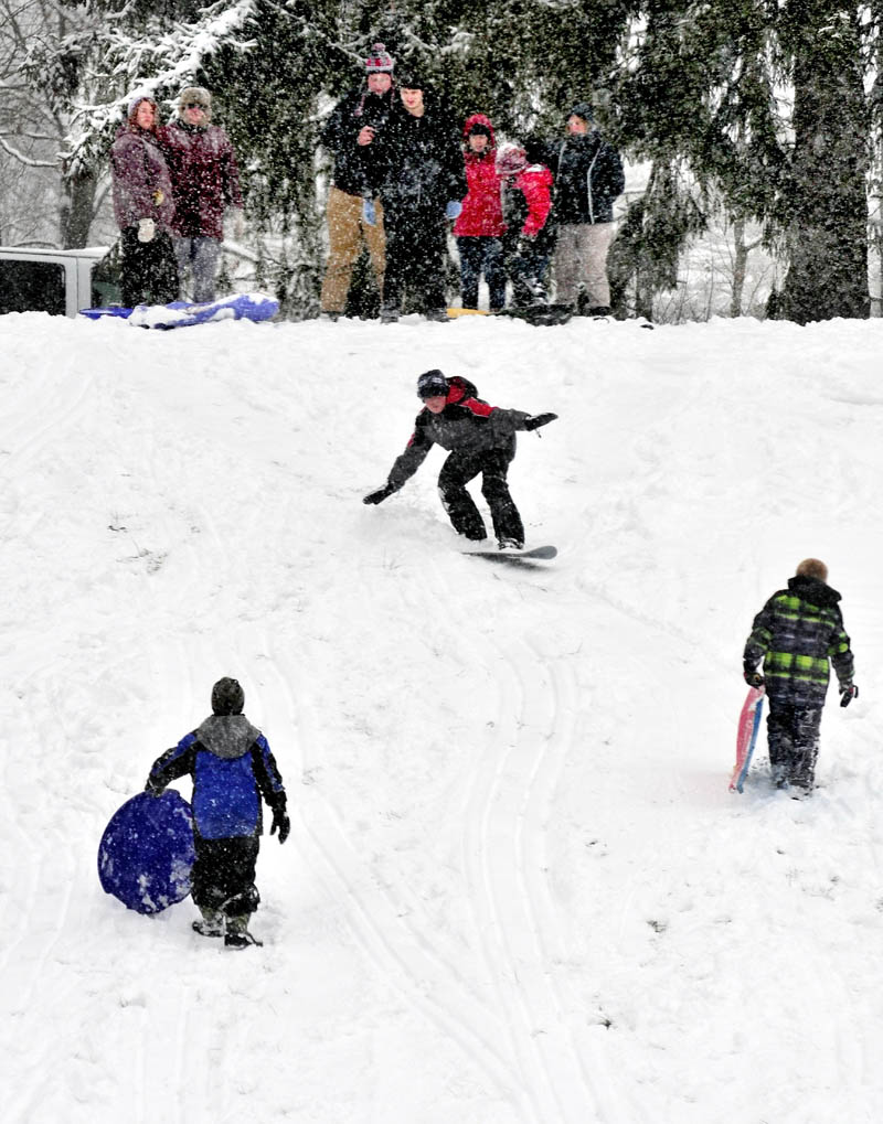 Students broke out sleds and snowboards to enjoy the fresh snowfall on a hill at the Good Will-Hinckley grounds in Fairfield on Monday.