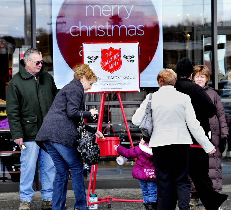 "Salvation Army bellringers Gary Mullins and his wife, Jean, at right, greet shoppers as Carol Noel helps her grandaughter, Peyton, drop money in the kettle at Elm Plaza in Waterville on Monday. ""People have been very generous,"" Gary Mullins said."