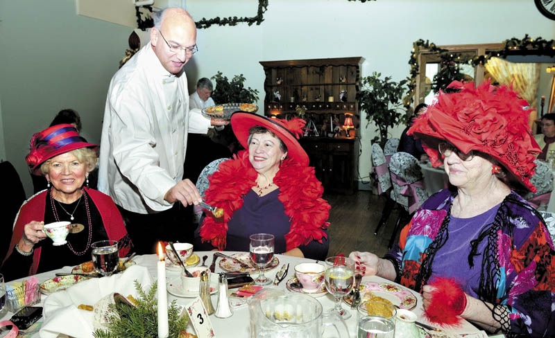 Roger Gagne serves members of the Foxy Gals chapter of the Red Hat Society during a Vintage Tea, at the Forum in Waterville on Sunday. Fine foods, entertainment and raffles were enjoyed. From left are Shirley Chaffee, Mary Audet and Jo Ann Eichorst.