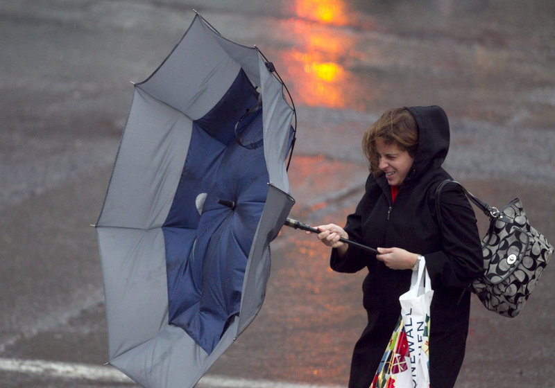 A woman reacts as a strong gust mangles her umbrella during a rain storm, Friday, Dec. 21, 2012, in Portland Maine. (AP Photo/Robert F. Bukaty)