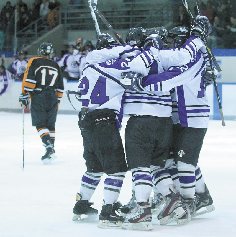 A REASON TO CELEBRATE: Waterville Senior High School's Edward Atkins is congratulated by teammates after scoring a second-period goal during the Panthers' 6-2 win over Winslow High School on Tuesday night in Waterville.