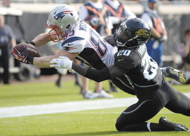 NICE EFFORT: New England Patriots wide receiver Wes Welker (83) dives over the goal line past Jacksonville Jaguars cornerback Mike Harris (20) for a touchdown on a 2-yard pass play during the Patriots' 23-16 win Sunday in Jacksonville, Fla. NFLACTION12;