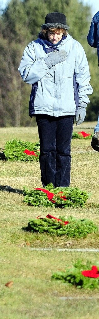 Suzanne Brochu, of Oakland, holds hand over her heart after placing a wreath on a ground-level markers in Maine Veterans Memorial Cemetery on Mount Vernon Road as part of Wreaths Across America events on Saturday. Her son, Army Pfc. Jordan M. Brochu, was killed in Afghanistan in 2009. Dozens of volunteers put 2,704 wreaths, from the Worcester Wreath Company, on veteran's graves at the Togus National Cemetery and the two Maine veterans cemeteries in Augusta, as part of Wreaths Across America events, which included laying of wreaths at Arlington National Cemetery.
