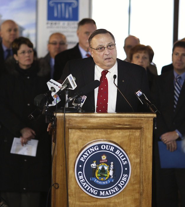 "Speaking from a podium with a slogan of ""Paying Our Bills, Creating Maine Jobs,"" Gov. Paul LePage held a press conference at the University of New England's College of Dental Medicine Patient Care Center Building, Tuesday, January 15, 2013, to announce his plan to pay hospitals back the $484 million they are owed by using future liquor-sale revenues as security against a bond that would pay the state's share of the hospital debt."