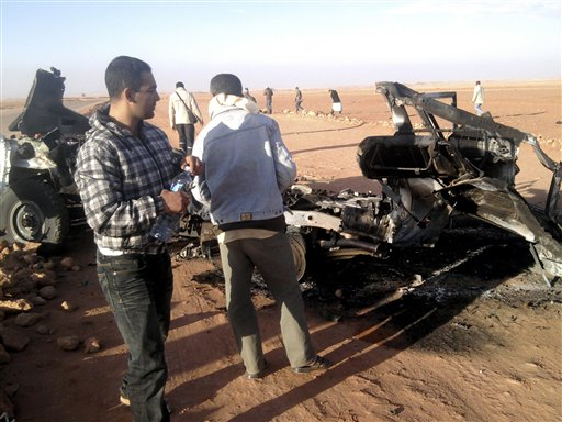 "In this undated photo, men look at the wreckage of a vehicle near Ain Amenas, Algeria. Algerian bomb squads scouring a gas plant where Islamist militants took dozens of foreign workers hostage found ""numerous"" new bodies on Sunday as they searched for explosive traps left behind by the attackers, a security official said."