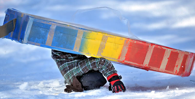 Cameron Louder flips his cardboard sled during the cardboard sled races at Lake George Regional Park during last year's Winter Carnival.