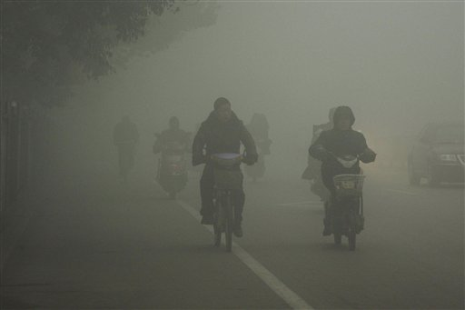 Cyclists travel on the road on a hazy day in Huaibei, in central China's Anhui province on Monday.