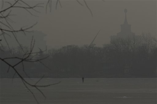 A man walks on an frozen lake on a hazy day in Beijing, China on Monday.