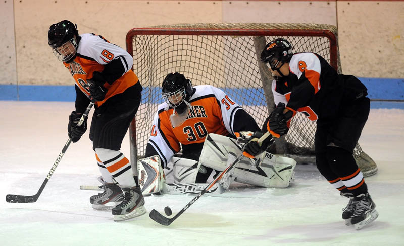 Staff photo by Michael G. Seamans FIND THE PUCK: Skowhegan's Chase Nelson, right, looks to shoot the puck on Gardiner goalie Brad Moore, center, as teammate Alex Hinckley, left, tries to defend in the second period Saturday night at Sukee Arena in Winslow.