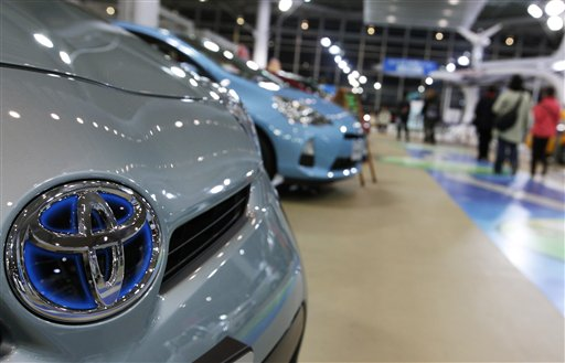 Visitors walk around a Toyota showroom in Tokyo recently. An analyst expects Toyota to keep the sales lead over GM this year as it launches a new Corolla.