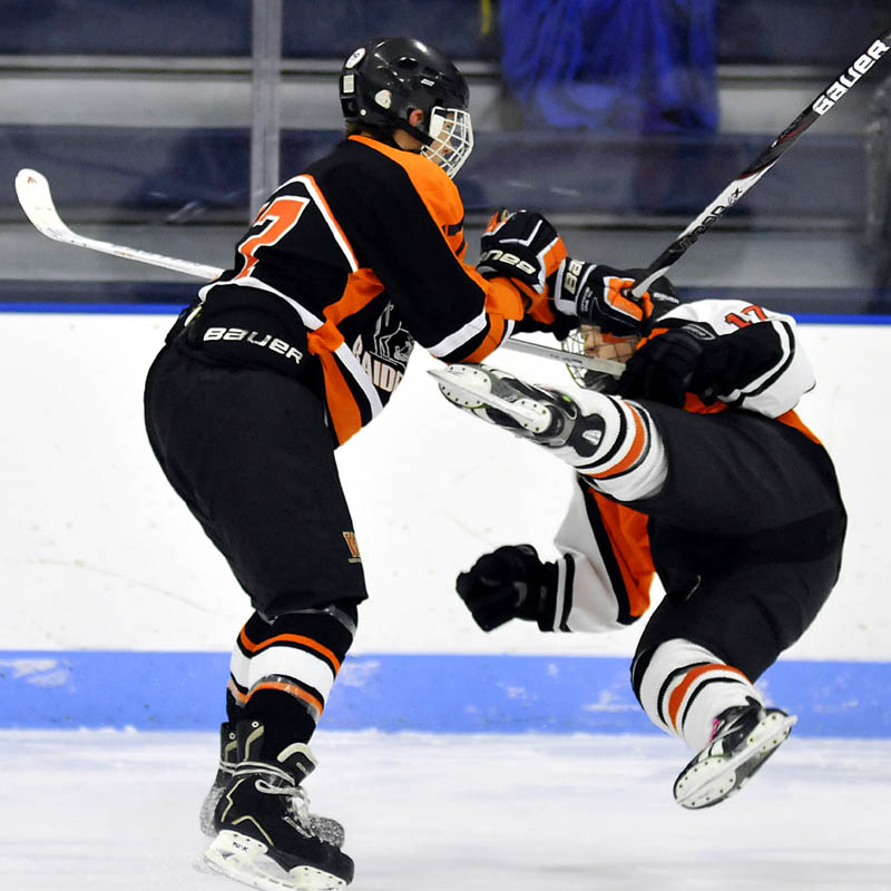 Winslow High School's Alex Berard, left, knocks down Gardiner Area High School's Dalton Sargent during their game Thursday at the Bank of Maine Ice Vault in Hallowell.