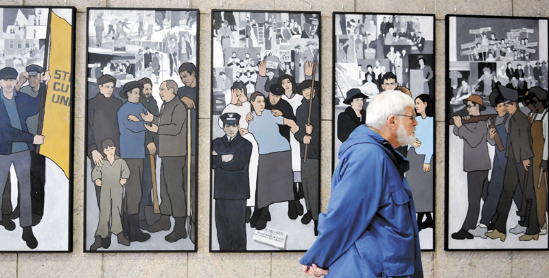 Ken Jones, of Farmingdale, examines the labor murals that are now hanging on the wall of the Cultural Building atrium that serves as the entryway to the Maine State Museum in Augusta Monday. The murals were hung over the weekend after being removed by Gov. Paul LePage in 2011 from the Department of Labor.