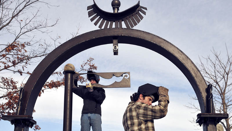 Aaron Dufour, left, replaces the top of a piece of the sculpture that he helped install Sunday with Ben Stoodley, right, and other classmates from the University of Maine at Augusta, at the Viles Arboretum in Augusta.